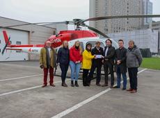 Een delegatie van het afdelingsbestuur overhandigt de symbolische enveloppe aan een piloot-vrijwilliger van de MUG-heli